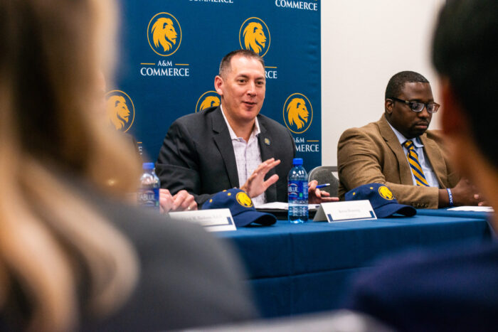 TAMUC Alumni talking to current students during an event.