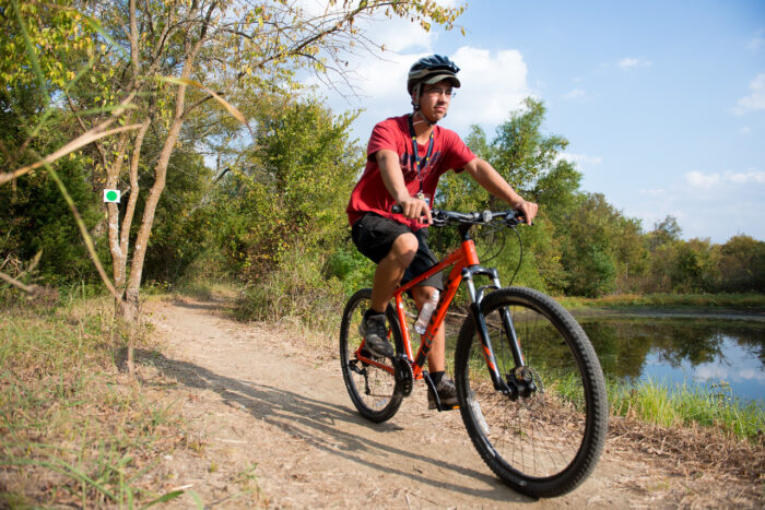 Student on a bike at the Campus Rec Trail.
