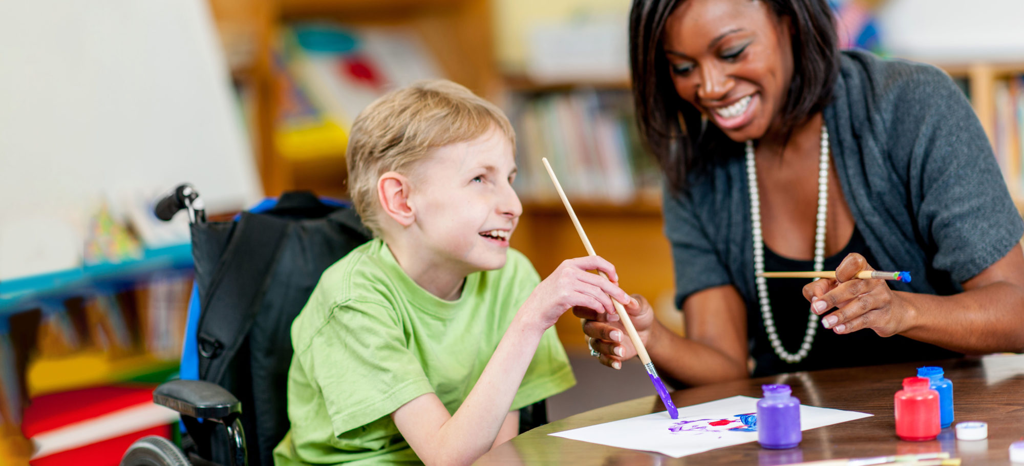 Special Education teacher interacting with student in a classroom.