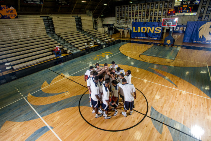 basketball team huddled around mid-court in practice.