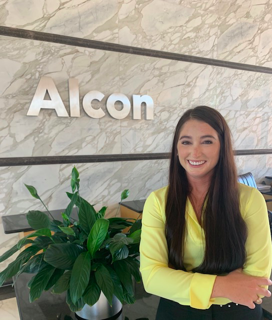 Photo of Alumni Hailey Bruening in front of Alcon sign.
