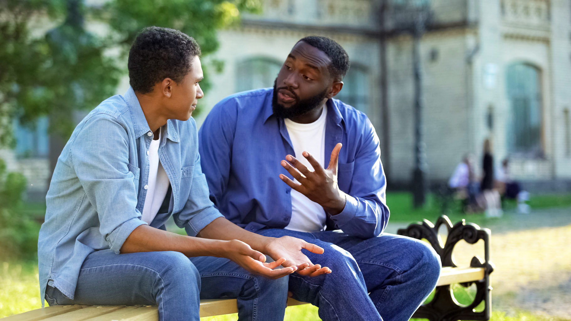 Father arguing teenage son sitting on campus bench, adolescent age difficulties.