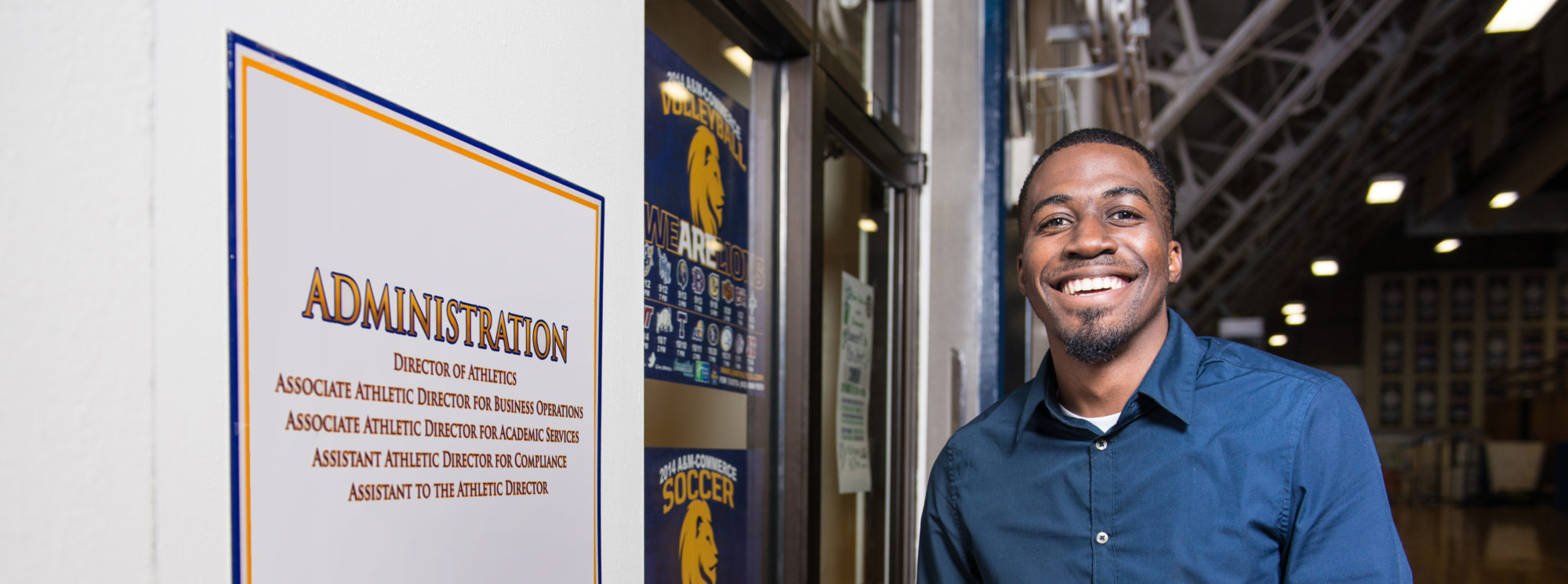 Athletic Administration Student smiling at the camera by the door of the TAMUC Athletics administration department.