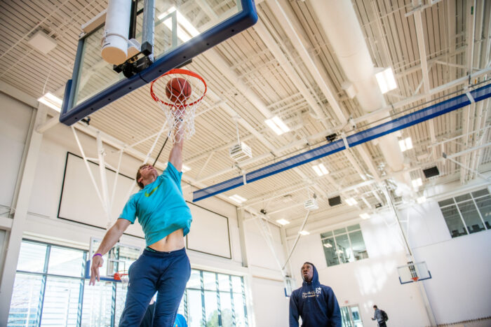 Male basketball player slam dunking a basketball