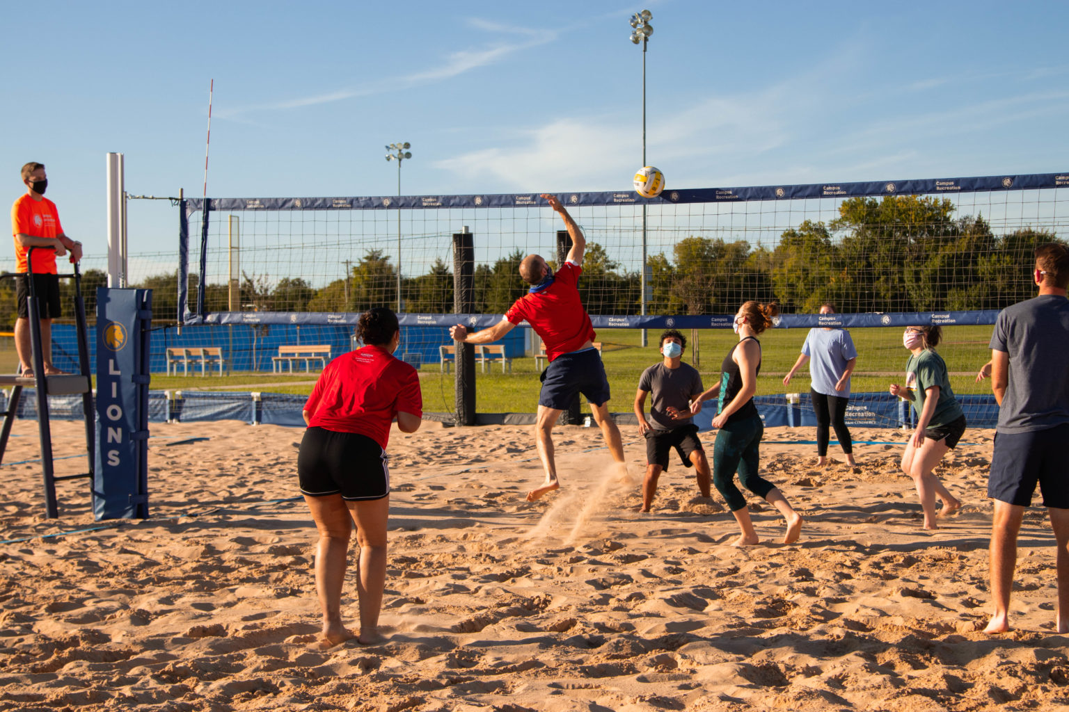A group of people playing sand volleyball at the Cain Sports Complex.