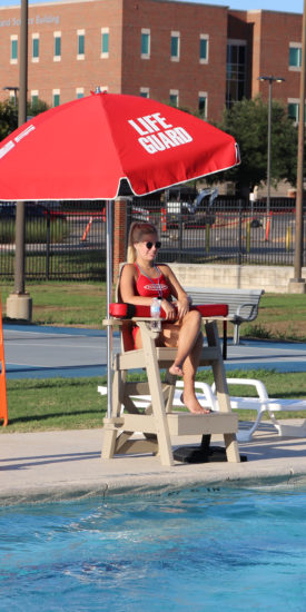 Life guard sitting by the pool.