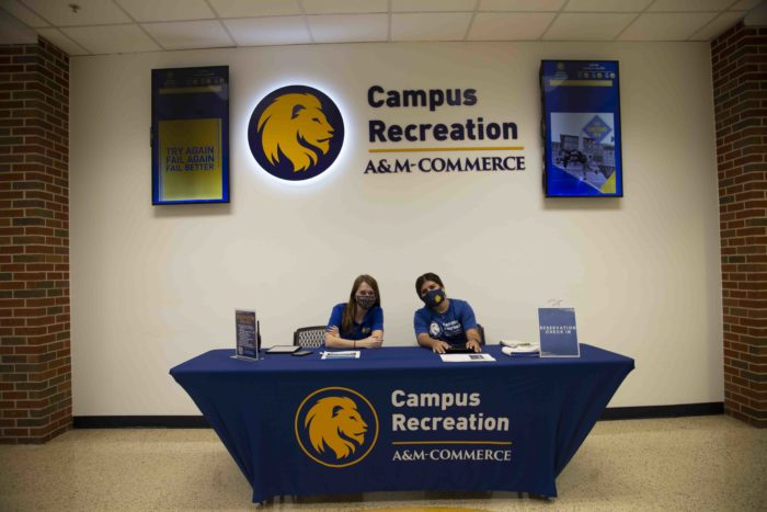 Two Campus Recreation employees wearing a mask sitting down at the check in table.