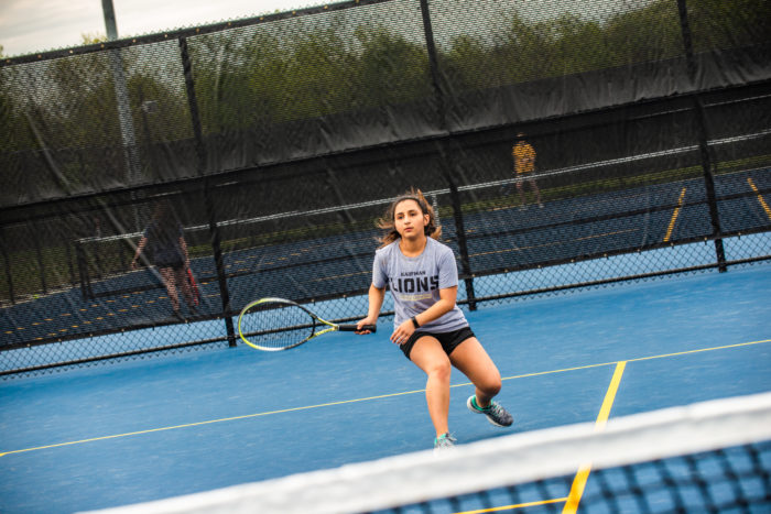 A student playing tennis.