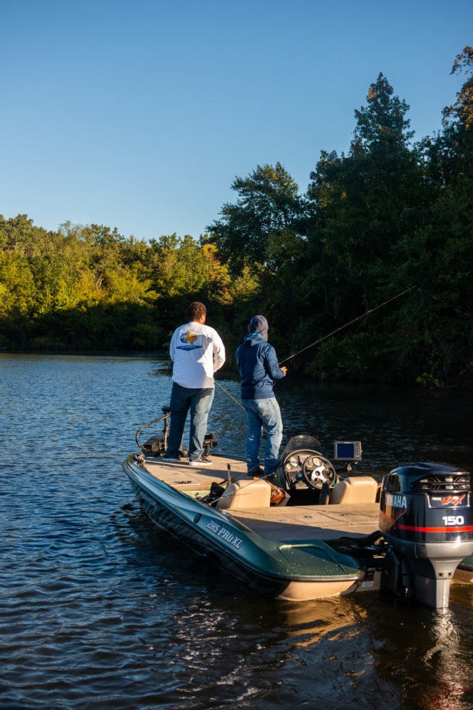 Two students on a boat fishing.
