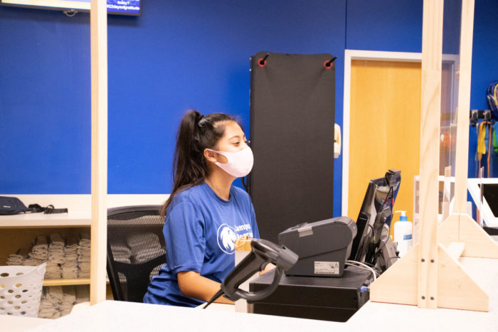 Campus Recreation employee behind the desk wearing a mask.