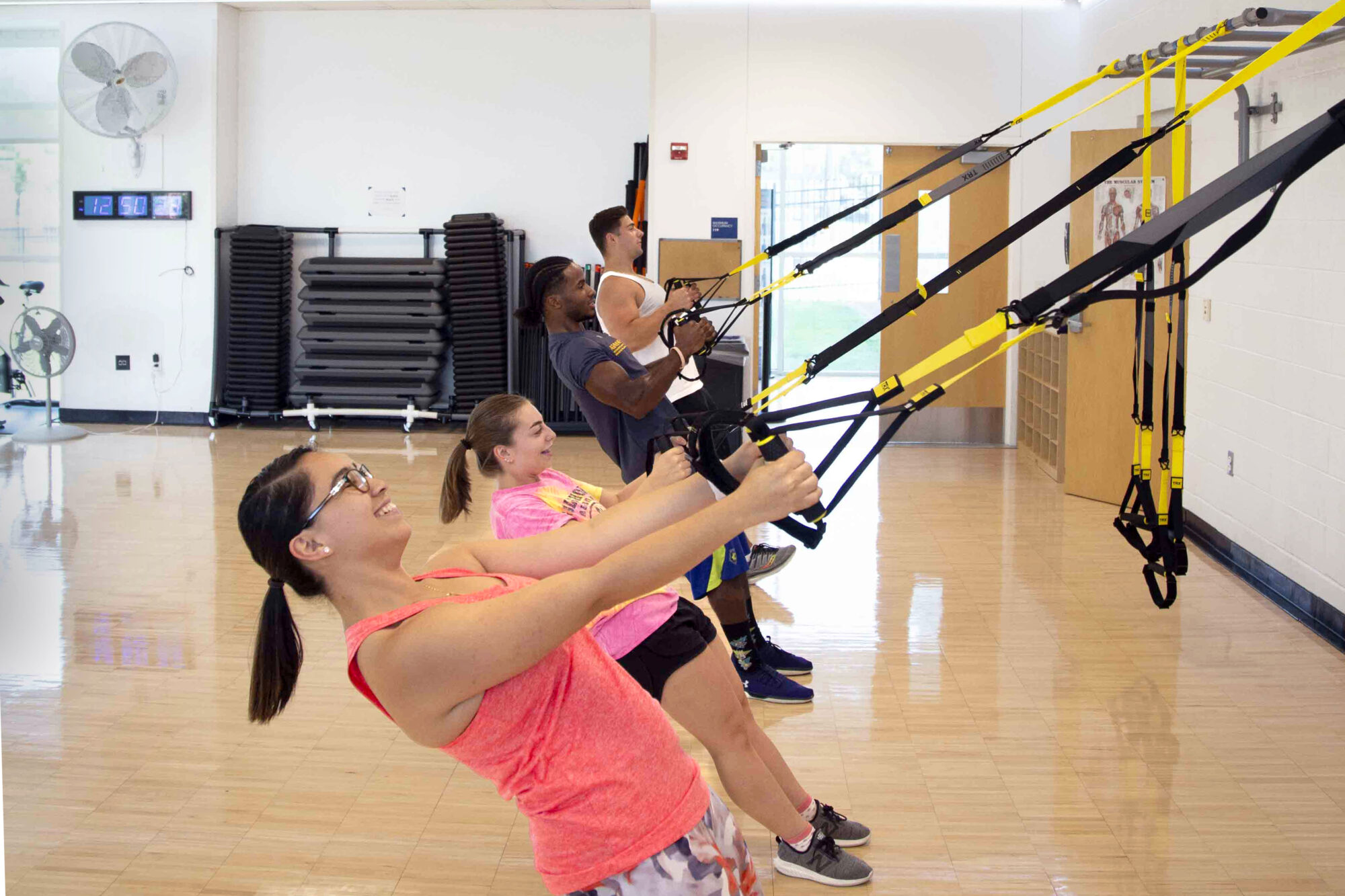 Students exercising using TRX bands during a group fitness class in the Activity Room.