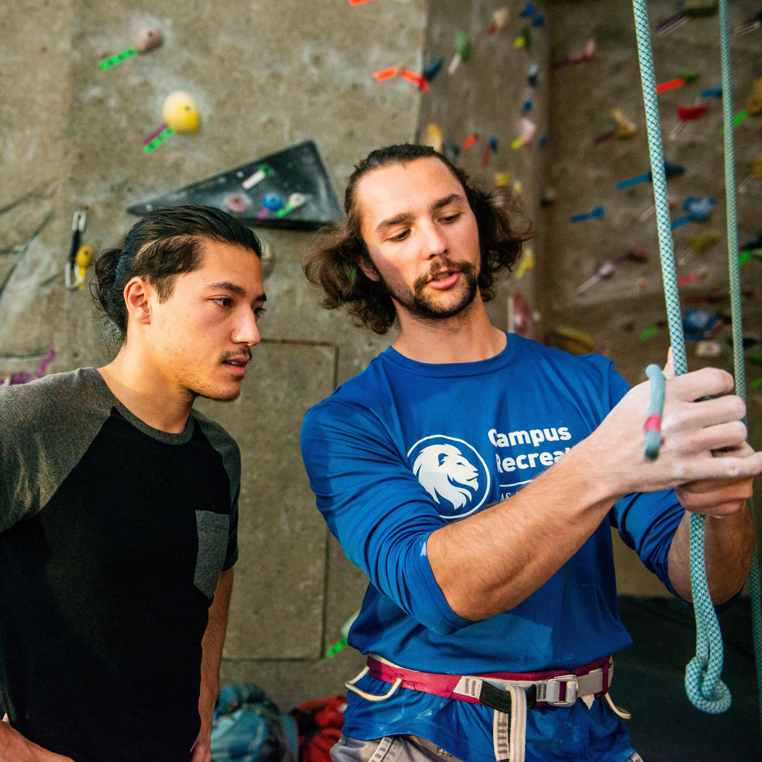 Rock climber instructing a student.