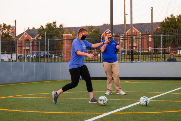 TAMUC student kicking a soccer ball.