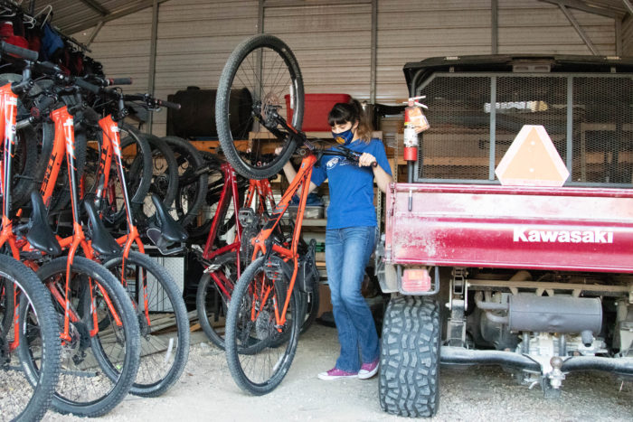 Outdoor adventure employee moving a bike.