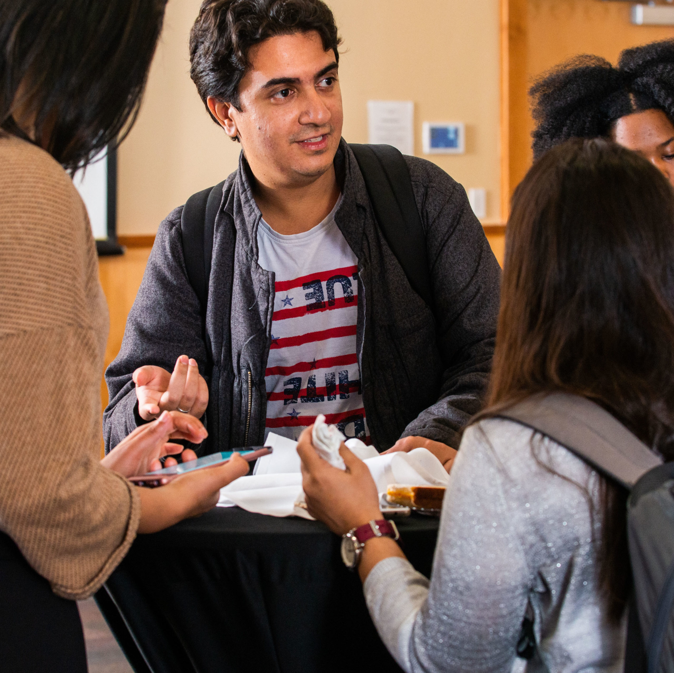 Students having a conversation around a table.