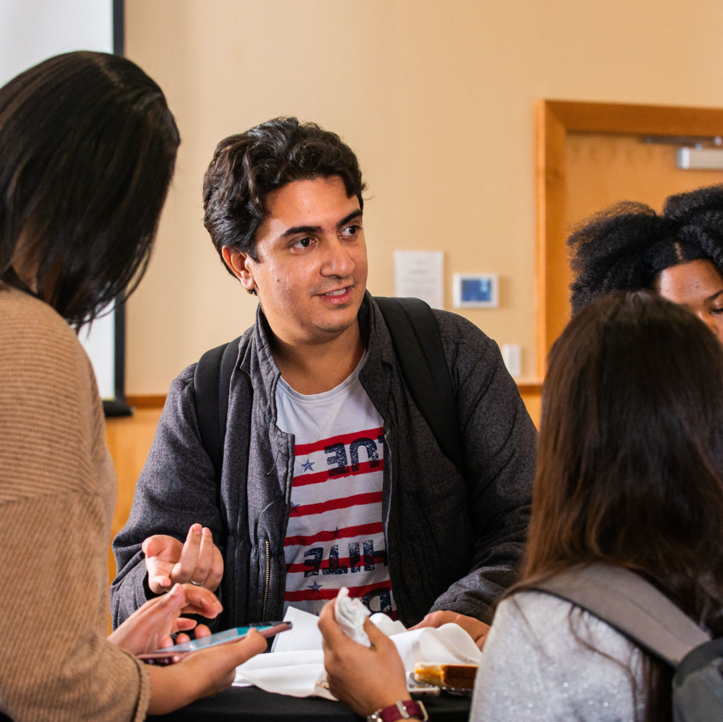 Students talking around a table.