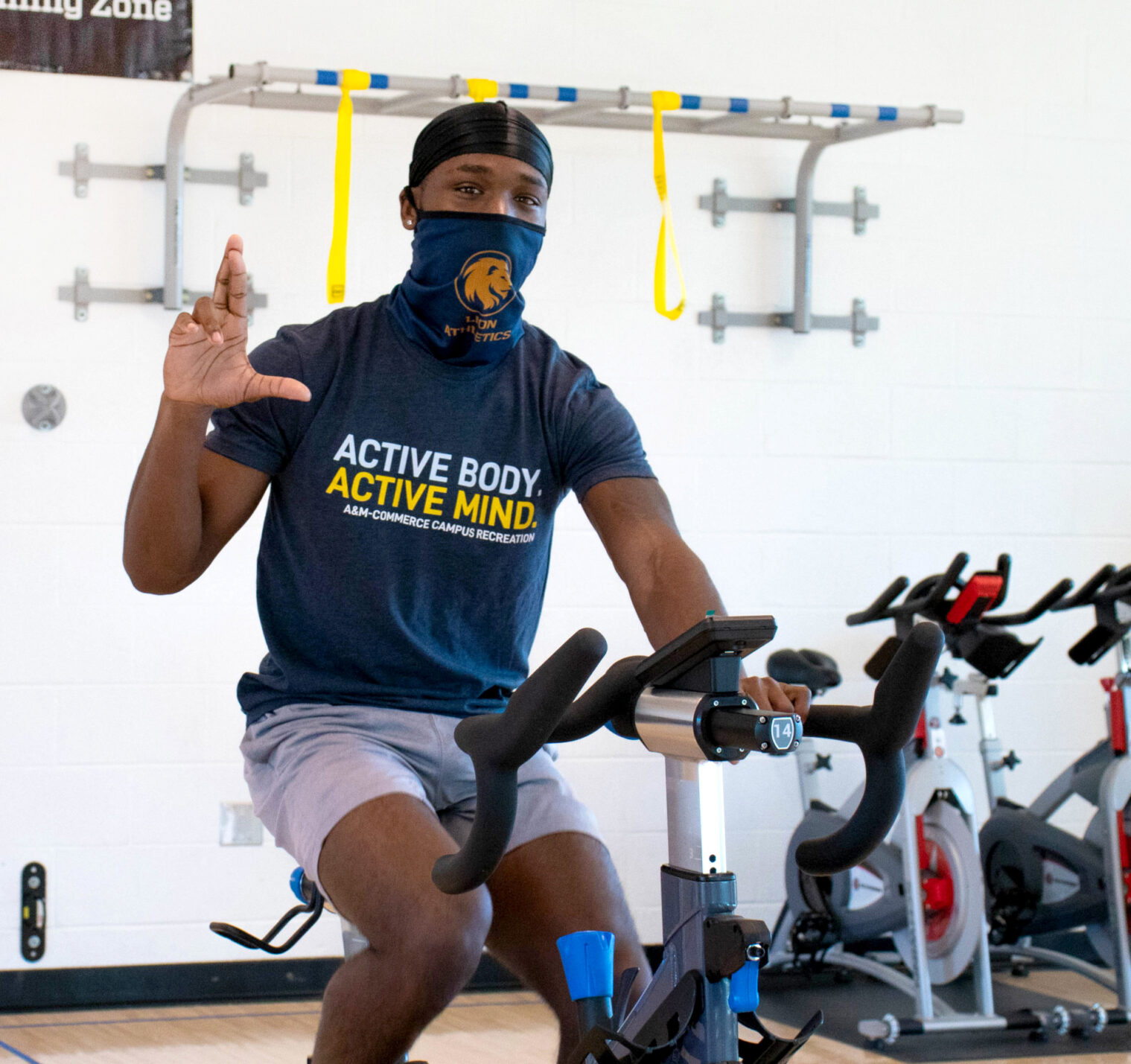 A&M-Commerce student during cycle class making the lion hand sign.