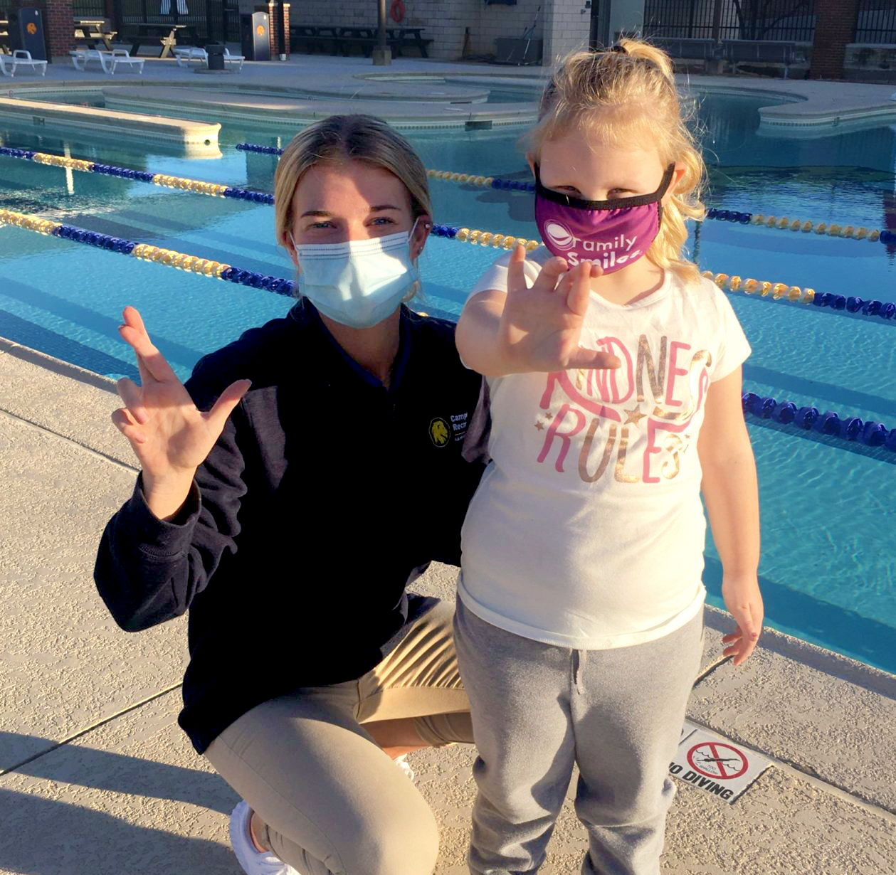 A campus Rec swim instructor with a young girl making the lion hand sing.