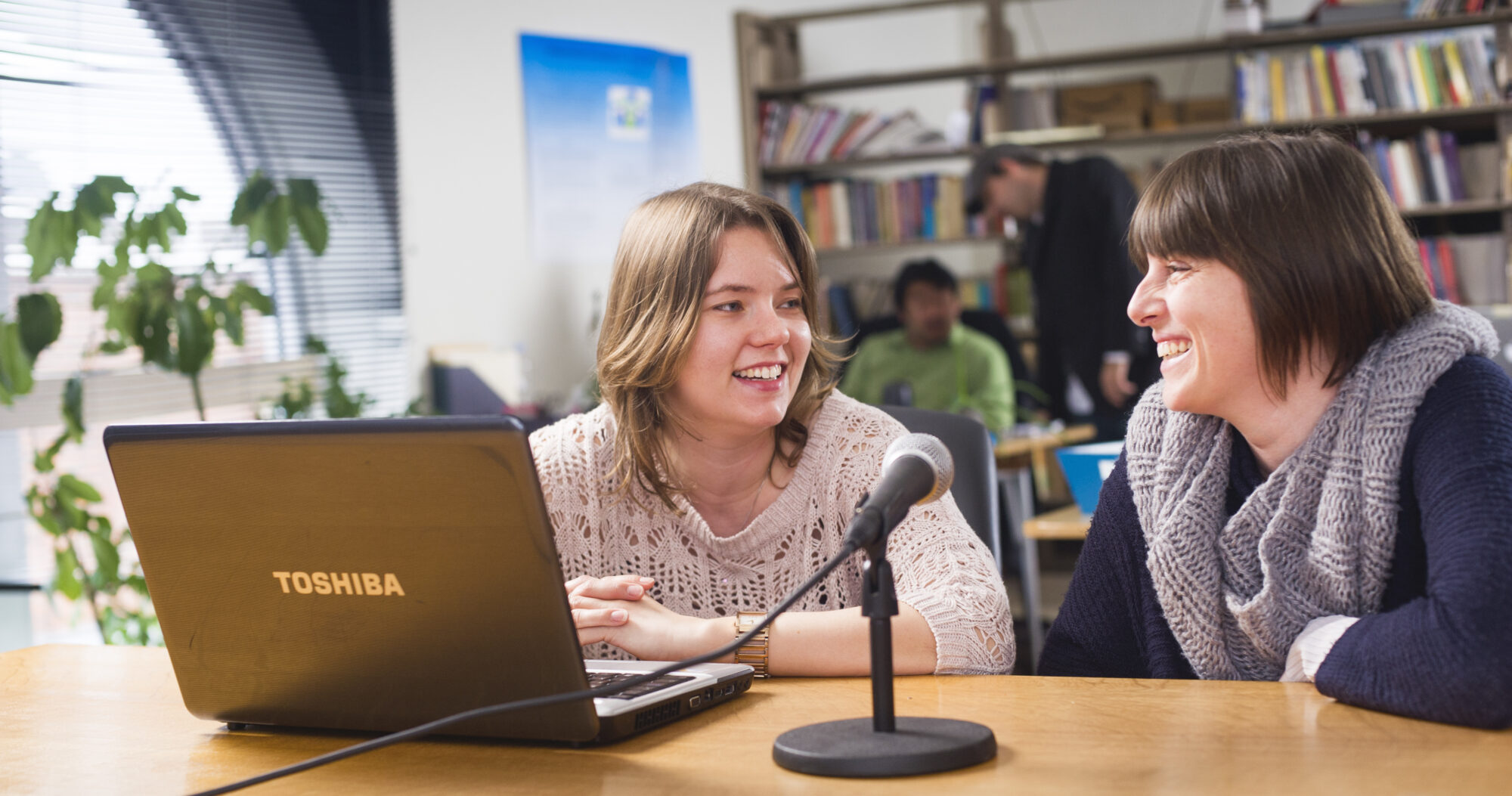 A professor and a student sitting down at a desk with a computer and a microphone in front of them.