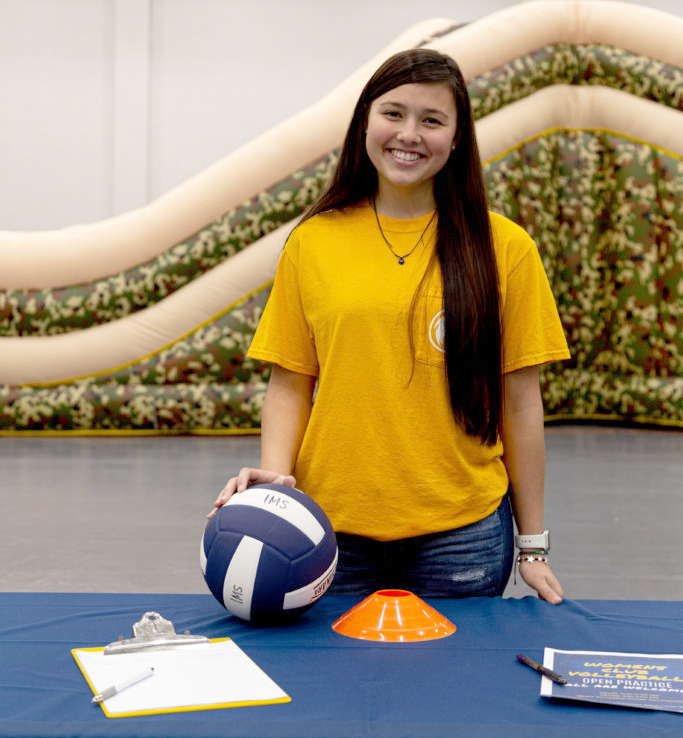 Member of the Women's volleyball club smiling at the camera in front of a table holding a volleyball.
