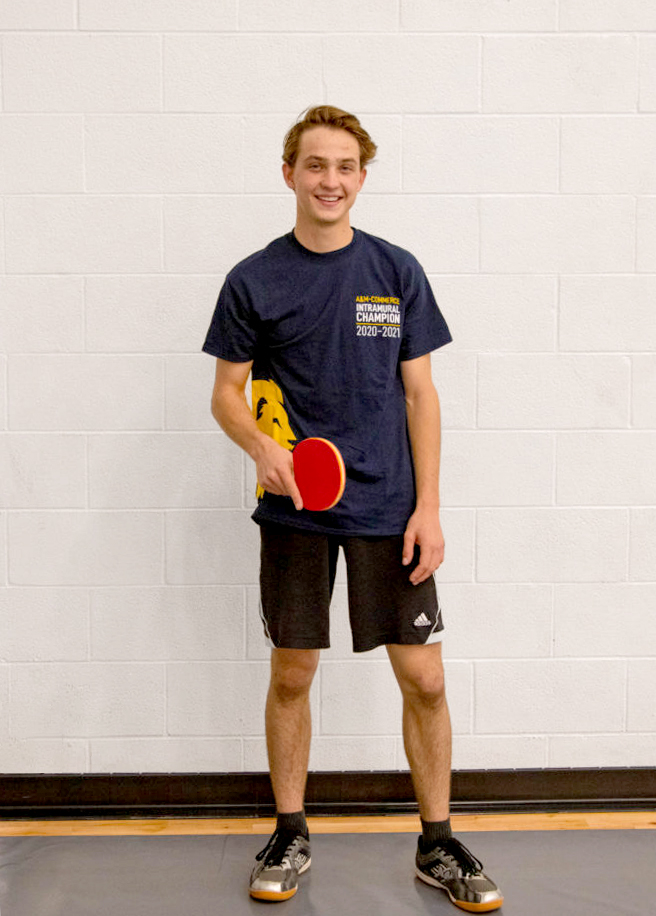 Member of the table tennis club smiling at the camera holding a Ping-Pong racket.