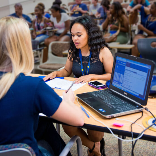 Female member of student success team meeting with female student during orientation.