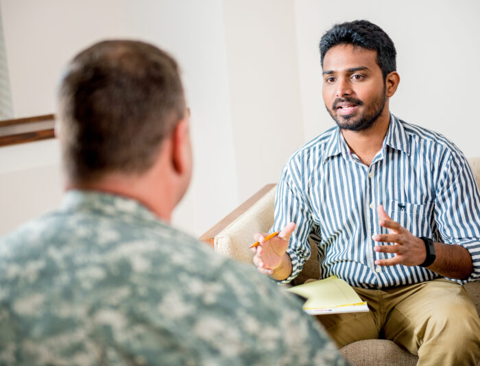 Social worker talking to man in the military.