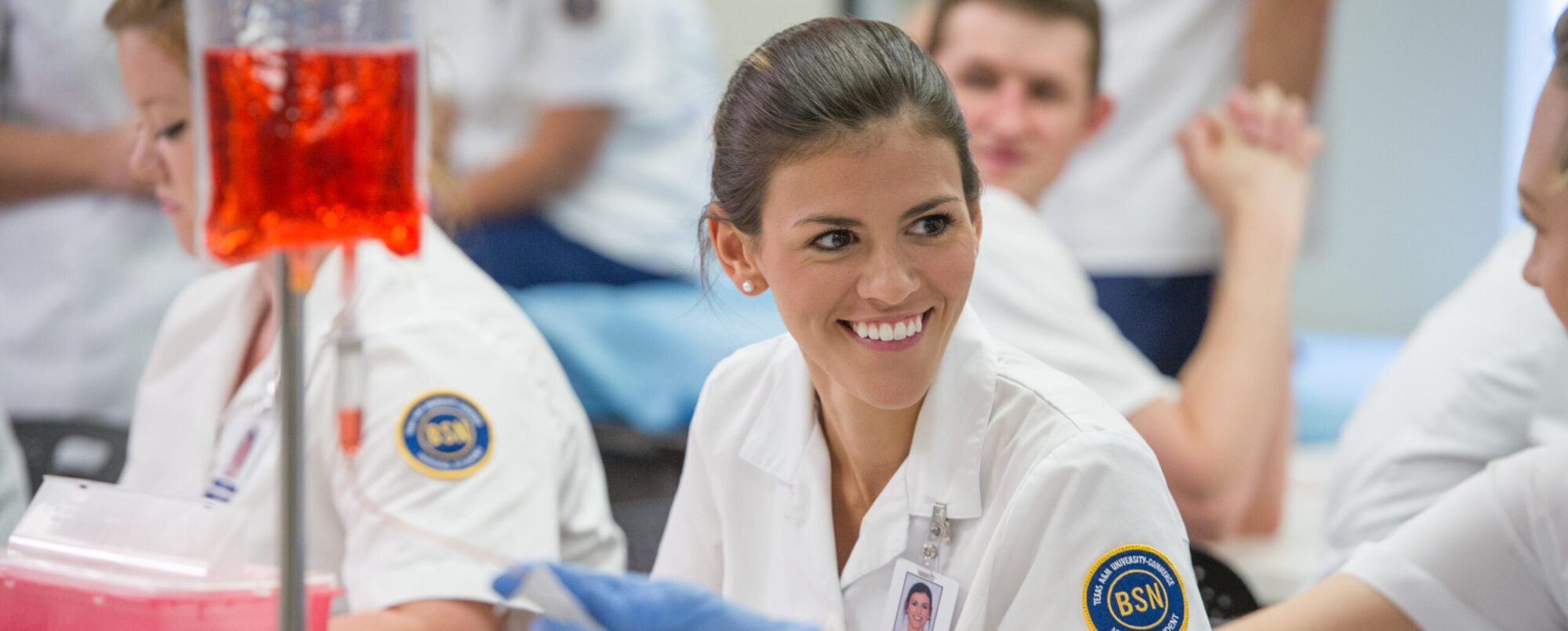 Nursing student in the lab with classmates.