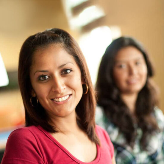 two females students smiling at the camera.