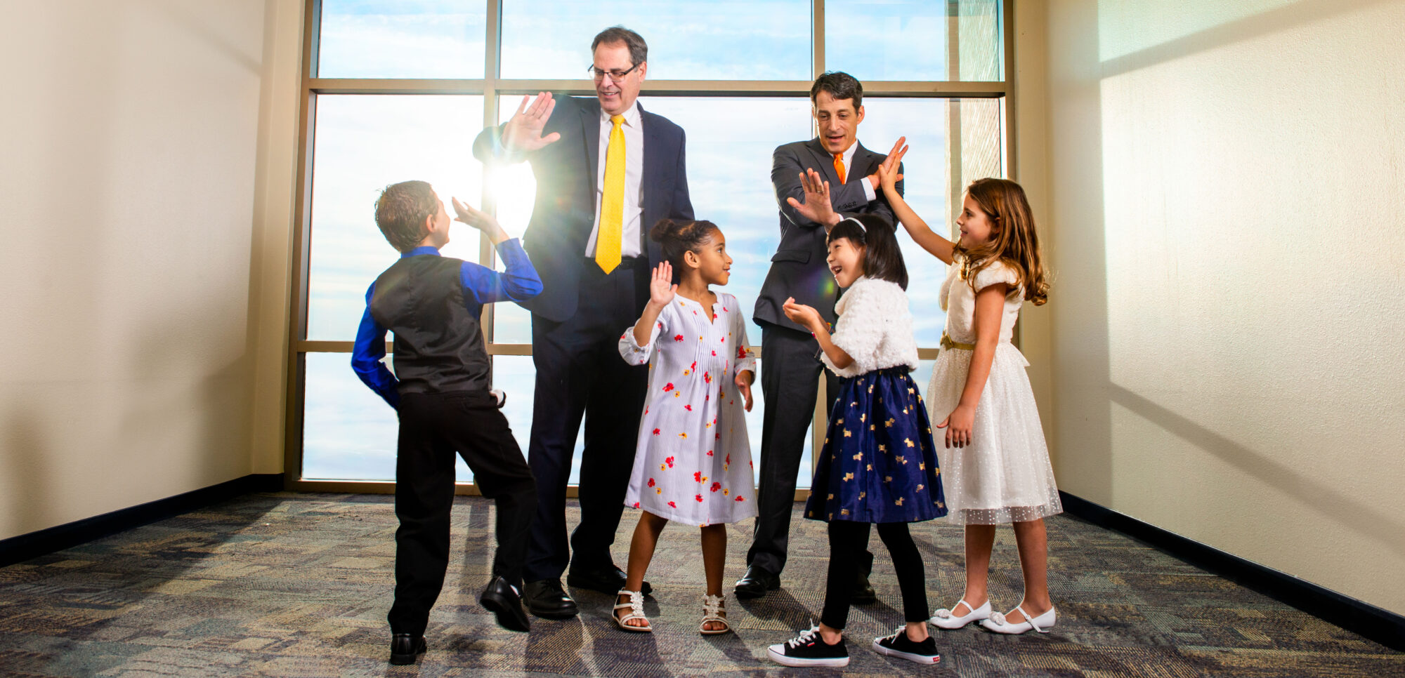 Two men giving four kids high fives.