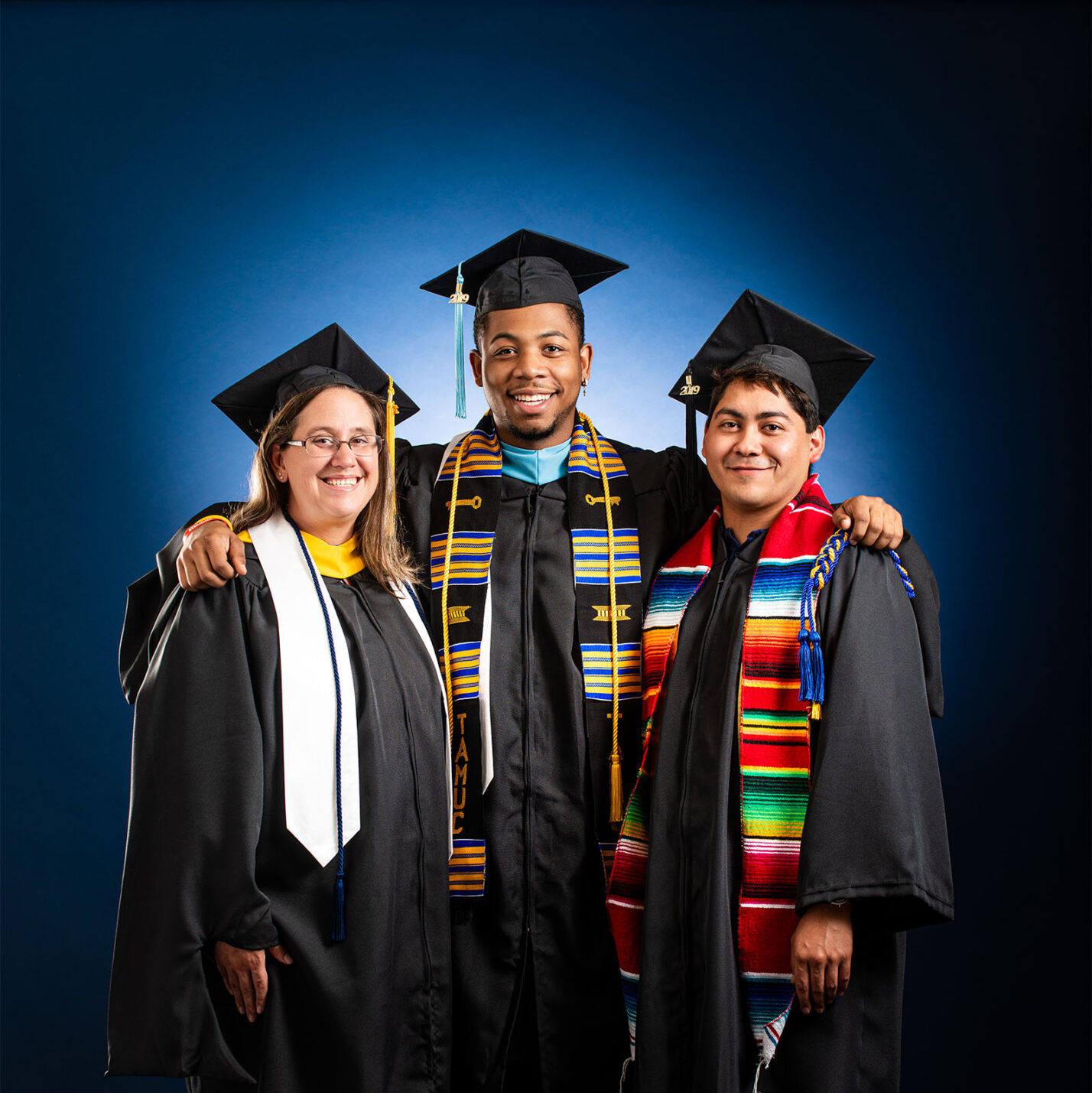 three students smiling at the camera in their cap and gown.