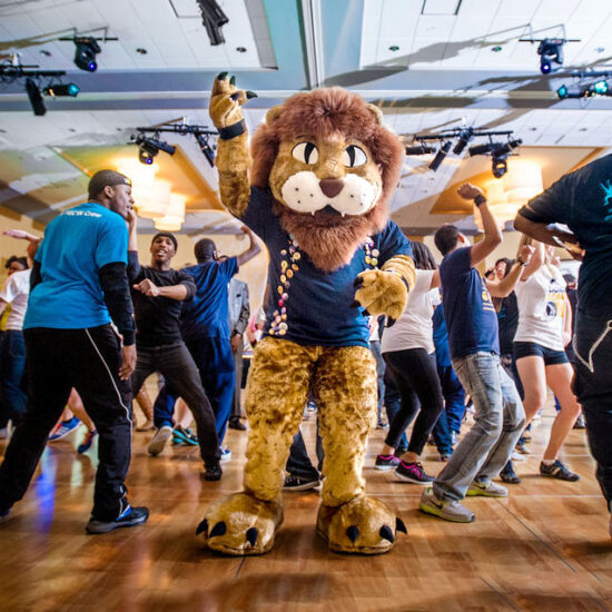 Lion mascot on the dance floor surrounded by students dancing.