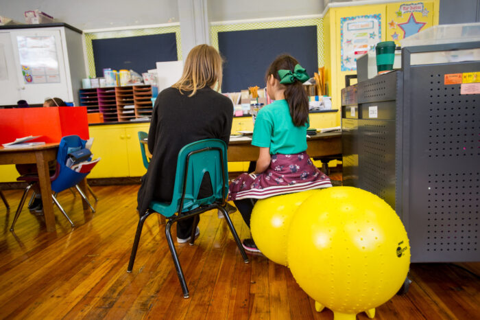 Teacher in a classroom with a young student.