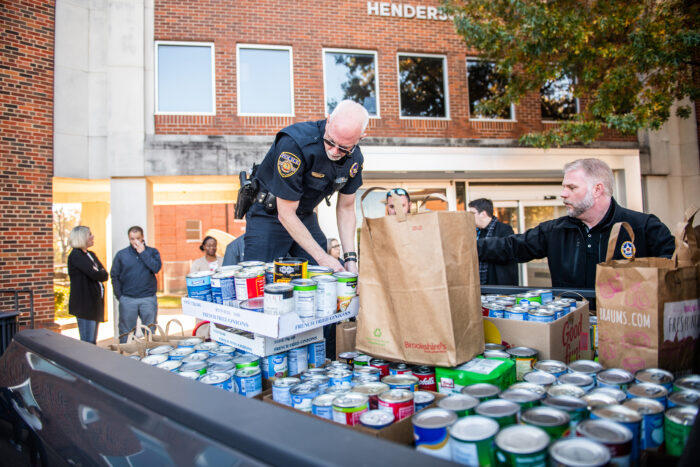 Officers helping load truck with food cans for donations.